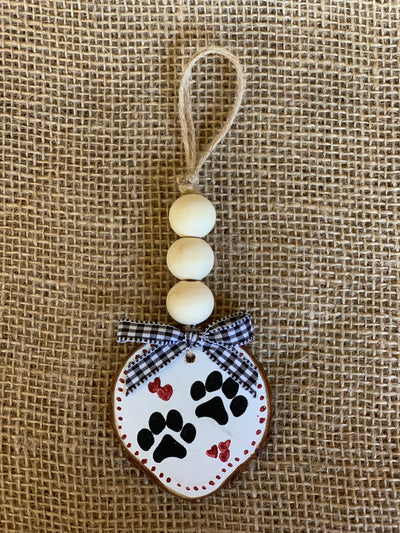 Animal Paw Wooden Beaded Ornament shows an image of a white painted background with black paw prints and red hearts with a plaid white and black bow.