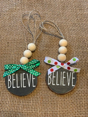 Believe Wooden Beaded Ornament shows an image of the black ornaments with two different bow selections.  Bows will vary due to demand.