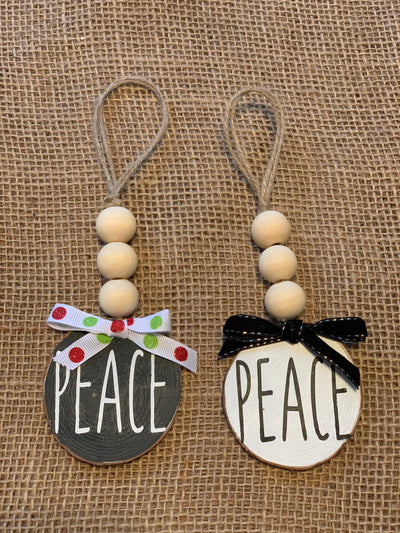 Peace Wooden Beaded Ornament shows an image of the black and white ornaments sitting on a table.  Each ornament sold separately.