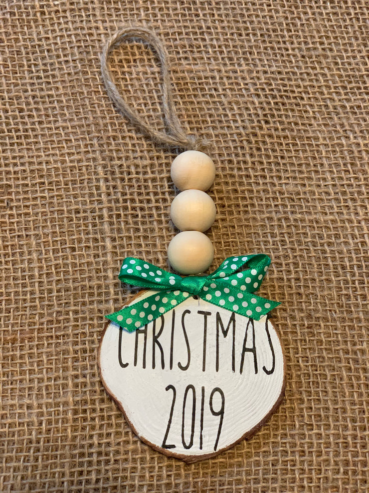 Christmas 2019 Wooden Beaded Ornament shows an image of the ornament sitting on a table.