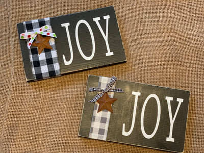 Joy Block Sign with Buffalo Check Ribbon shows the two different signs sitting side by side.  Each sign sold separately.