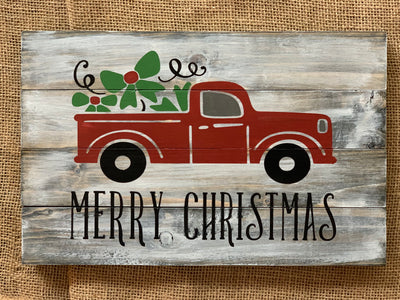 Merry Christmas (Red Truck) Pallet Sign is displayed sitting on a table.
