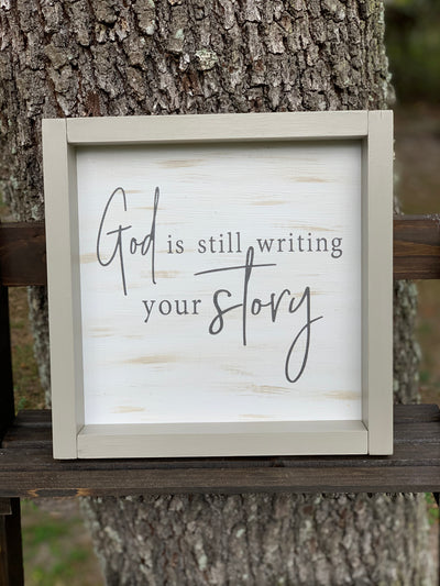 God Is Still Writing Your Story shows an image of the sign sitting on a ladder outside.
