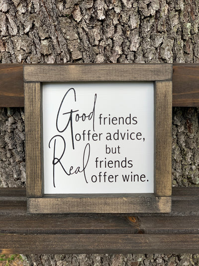 Good Friends Offer Advice, But Real Friends Offer Wine (Script Version) shows the sign sitting outside on a ladder.