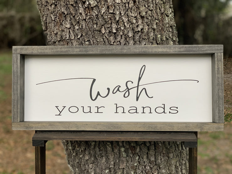 Wash Your Hands is displayed sitting outside on a ladder.  This sign shows the all black hand painted lettering.