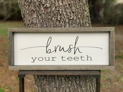 Brush Your Teeth is displayed sitting outside on a ladder.  This sign shows the all black lettering.