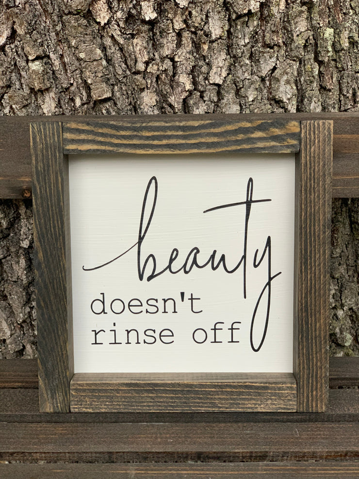 Beauty Doesn't Rinse Off displays the sign sitting outside on a ladder.