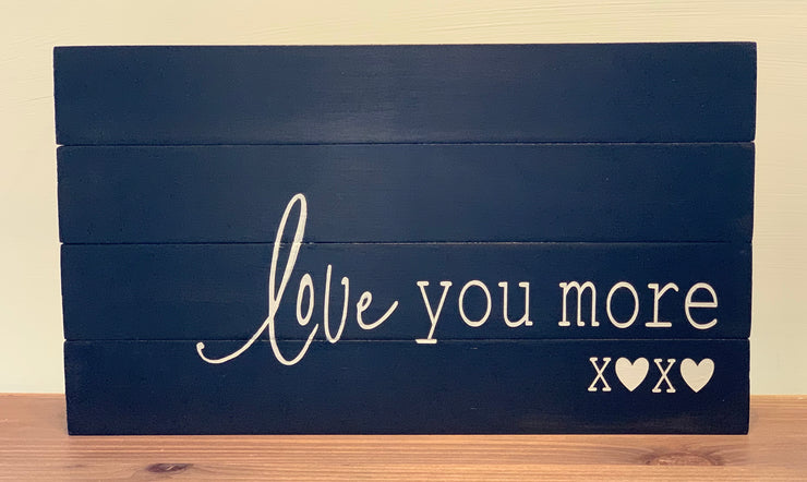 Love you more sign is displayed sitting on a shelf.  This pallet board is painted black with white hand painted lettering.