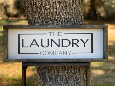 The Laundry Company shows the sign sitting outside on a ladder.
