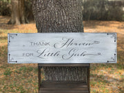 Thank Heaven For Little Girls (Distressed Wood Sign) is displayed outside sitting on a ladder.