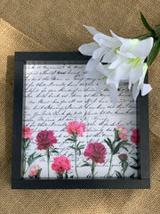 The Vintage Letter is shown laying on a burlap table with a floral stem beside it.