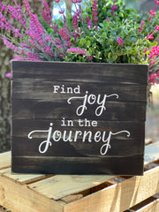 Find Joy In The Journey (April 2020 Sign of the Month) is shown sitting outside with a floral arrangement.
