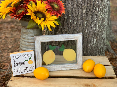 Lemon Glass Picture Frame is paired with our Easy Peasy Lemon Squeezy small block sign, a metal pitcher with sunflowers and a display of lemons.  Each item sold separately.