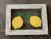 Lemon Glass Picture Frame is shown sitting on a table, to visually see the hand painted lemons.