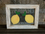 Lemon Glass Picture Frame is sitting on a shelf.  You can see the transparent glass frame is visible to the other side.