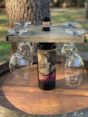 Wood Wine Glass Holder is shown with the aged stain and a set of 4 etched wine glasses sitting on top of a wine barrel.