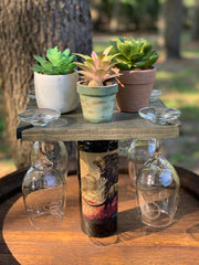 Wood Wine Glass Holder is shown with the wood holder, set of 4 humorous etched wine glasses, a bottle of wine, and three succulent small plants.