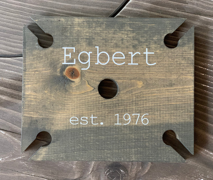 This image shows the Wood Wine Glass Holder with the family name and date hand painted in linen white.
