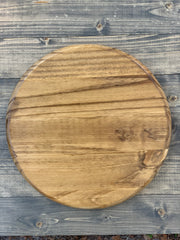 Customizable Round Sign is shown in the natural stain laying on the aged wine barrel stain color.
