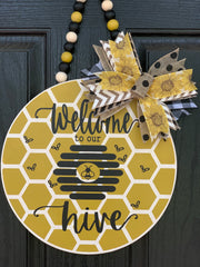 Welcome To Our Hive Beaded Garland Door or Wall Hanger shows an image of the door hanger hanging on the front door.