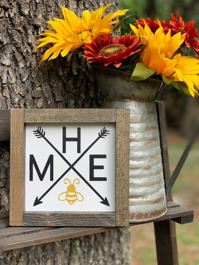 Home (Bee) Sign is shown sitting on a ladder with a rustic pitcher of flowers.