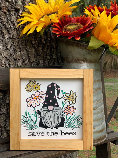 Save The Bees Gnome Sign is shown sitting outside on a ladder with a rustic pitcher of flowers.