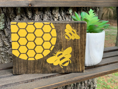 Honeycomb Small Block Bee Sign is shown sitting on a ladder shown with a succulent.