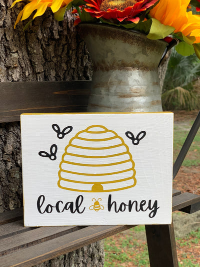 Local Honey Beehive Block Sign is shown sitting outside on a ladder with a rustic pitcher of flowers.