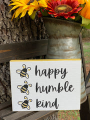 Bee Happy, Bee Humble, Bee Kind is shown sitting outside on a ladder with a rustic pitcher full of flowers.