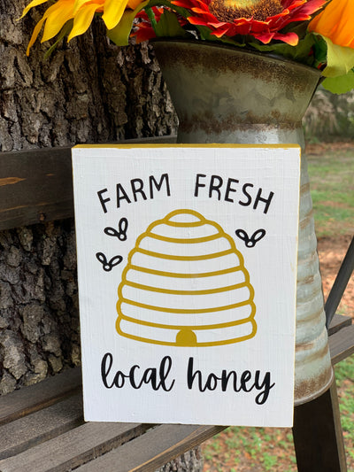 Farm Fresh Local Honey is shown sitting on a ladder with a rustic pitcher full of flowers.