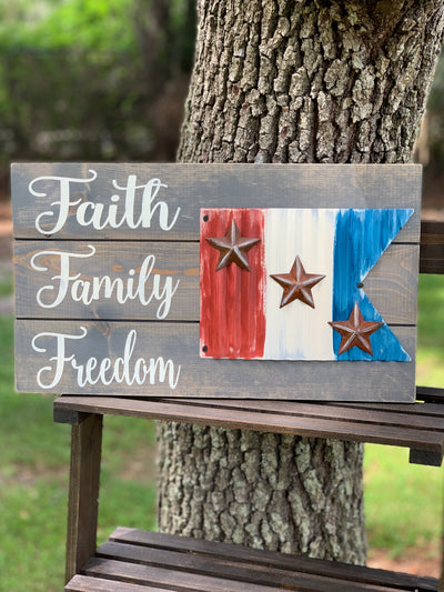 Faith Family Freedom Metal Flag Pallet Board is shown sitting outside on a ladder.  This sign has a red, white and blue stripe metal painted flag with rustic metal stars.