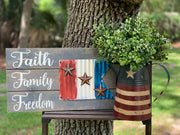 Faith Family Freedom Metal Flag Pallet Board is shown with a primitive pitcher filled with greenery.  Each item it sold separately.