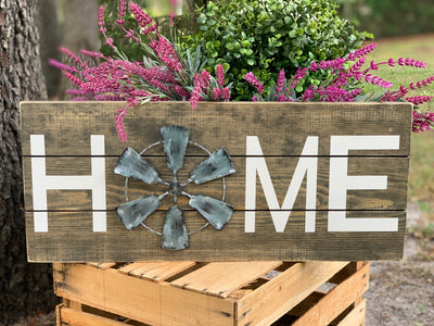 Home Windmill Pallet Board Sign  shows an image of the home sign sitting outside with a flower bucket.