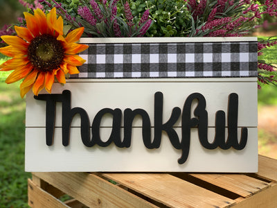 "Thankful Script Pallet Board Sign is shown sitting outside on a crate.  This sign has a black and white buffalo check plaid ribbon at the top with an orange and yellow sunflower in the corner.  It's on a white pallet board with black script thankful attached.  Has a sawtooth hook to hang or can be placed on a shelf.  This sign measures 16x9.25""."
