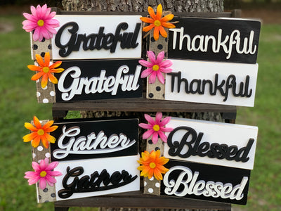 "Mini Gratitude Signs. Choose from white or black wood block that measures 9 x 3.5"".  Choose from the words grateful, gather, thankful or blessed.  Each has a burlap ribbon with either a pink or orange daisy attached."