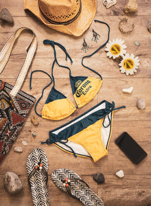 Ladies Corona Bikini- Corona Extra (Blue & Gold) String Bikini Lifestyle Photo with Tote Bag, Sandals and Sunglasses