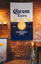 "Load image into Gallery viewer, Corona Indoor Wall Banner- Corona Label (30"" by 50"") Banner Hanging ON Brick Wall"