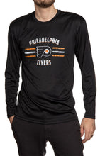 Load image into Gallery viewer, Men's Officially Licensed NHL Distressed Lines Long Sleeve Performance Rashguard Wicking Shirt- Philadelphia Flyers Man Wearing Long Sleeve Shirt With Hand In Pocket