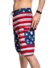 Load image into Gallery viewer, Men's USA Flag Distressed Boardshorts- Barnboard Side View With Man Putting Phone In Side Pocket