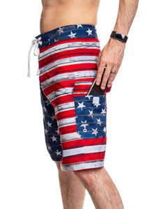 Men's USA Flag Distressed Boardshorts- Barnboard Side View With Man Putting Phone In Side Pocket