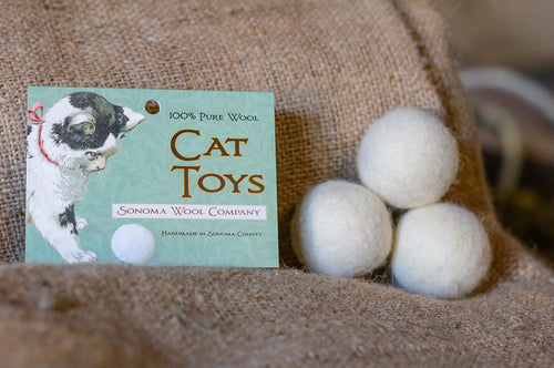 3 small Sonoma Wool Company wool ball cat toys stacked on burlap, next to cardboard tent card Cat Toy label