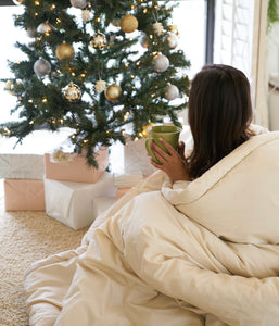 Wool Comforter wrapped around woman in front of holiday tree
