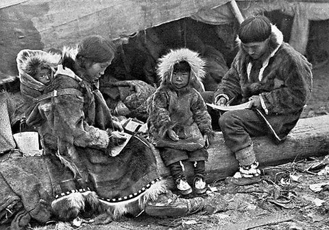 Eskimo family with the child being carried on the mother's back in a fur lined carrier. Dated 1917. National Geographic Magazine, Volume 31 (1917), page 564