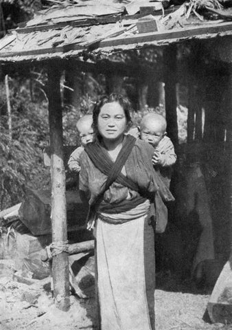 Japan – a mother carrying both her children on her back at once using a cloth carrier.