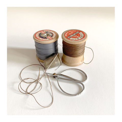 A selection of sewing threads, with a needle, thimble and scissors