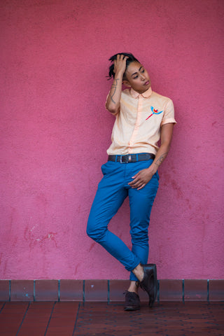 Los-Angeles-based-queer-Asian-LGBTQ-Tomboy-model-and-entrepreneur-Joss-TM-posing-against-pink-wall-wearing-light-orange-short-sleeve-button-up-shirt-blue-chino-pants-and-brown-dress-shoes