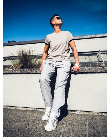 Tomboy-Model-Blue-Sky-Sunny-Day-Short-Hair-Fade-Sand-Colour-T-shirt-Light-Grey-Joggers-White-Sneakers-Silver-Black-Bracelet-Gender-Neutral-Androgynous-Summer-Fashion