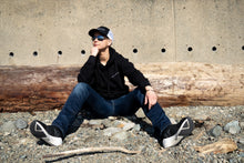 Load image into Gallery viewer, Tomboy-Model-Ocean-Beach-Snapback-Black-Hoodie-Blue-Jeans-Aviator-Sunglasses-Silver-Bracelet-Gender-Neutral-Nonbinary-Androgynous-Summer-Fashion.jpg