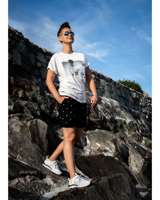 Tomboy Model, Sunny Beach, Short Hair Fade, Palm Tree White Graphic T-shirt, Palm Tree Print Navy Shorts, White Puma Sneakers, Silver Bracelet, Gender Neutral, Androgynous, Summer Fashion