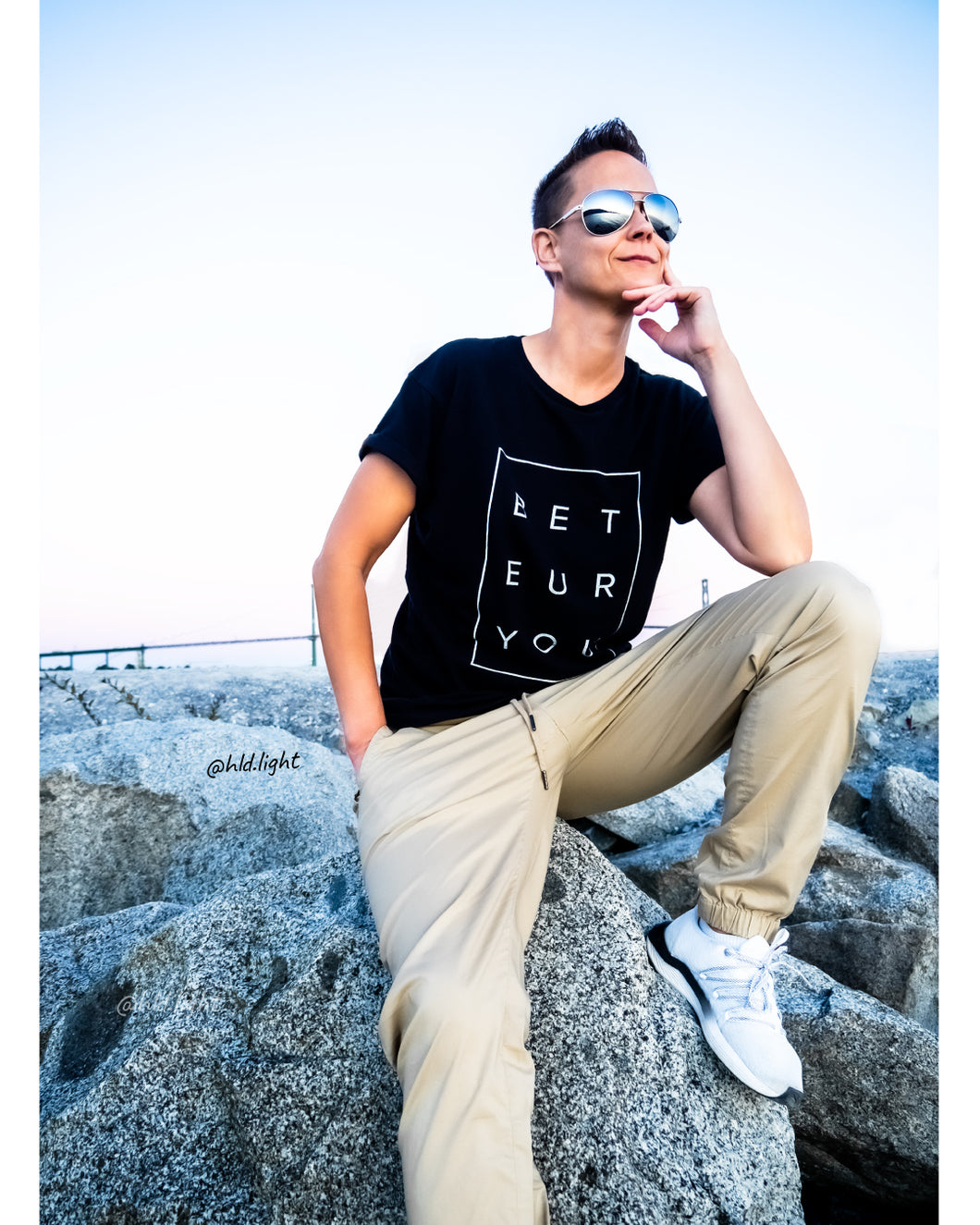 Tomboy-Model-Sunset-Beach-Tomboy-Style-Short-Hair-Aviator-Sunglasses-Black-T-shirt-Be-You-Puzzle-Calvin-Klein-Khaki-Joggers-White-Puma-Sneakers-Gender-Neutral-Androgynous-Fashion